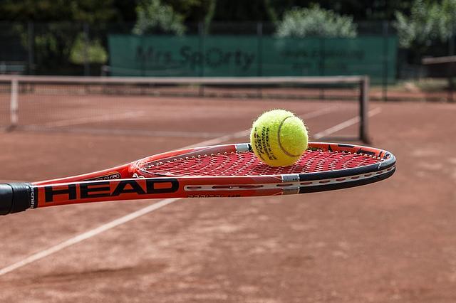 Tennisschläger mit Tennisball auf der Schlägerpfanne