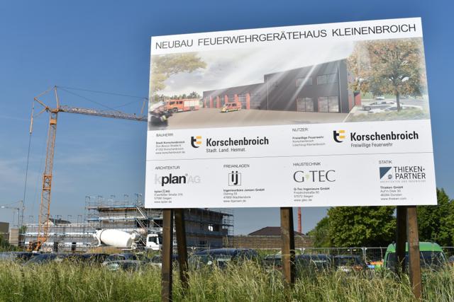 Baustellenschild und Bautätigkeit mit Kran im Hintergrund