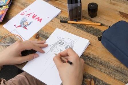Jugendliche zeichnen Mangas auf Papier.