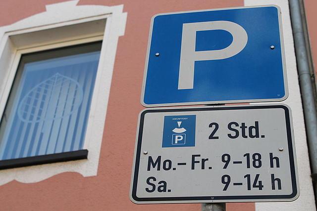 Parkplatzschild mit Hinweis auf Parkscheibenpflicht vor rosafarbenem Haus