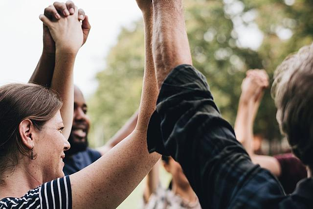 Menschen verschiedener Nationalitäten halten sich an den Händen