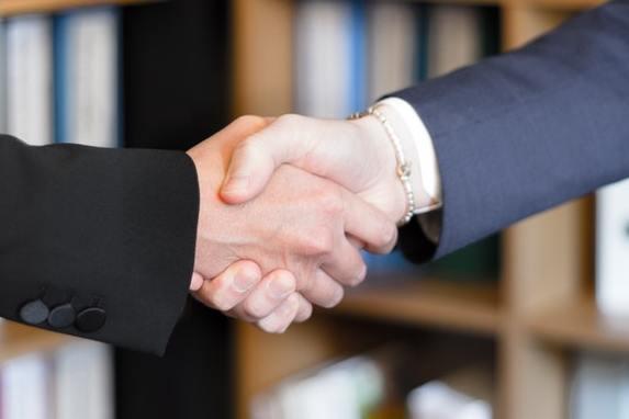Zwei Menschen reichen sich die Hand vor Regal mit Aktenordnern