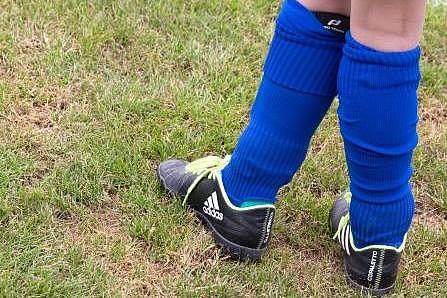 Deatilaufnahme von Kinderbeinen mit Fußballschuhen und Knieschonern
