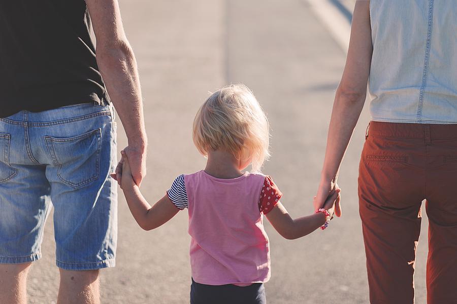 Vater, Mutter und Kind in der Mitte von hinten fotografiert gehen eine Straße entlang