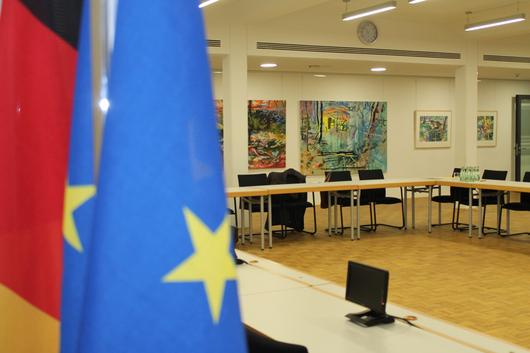 Blick in den Ratssaal mit Europaflagge und Deutschlandflagge im Vordergrund