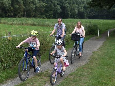vierköpfige Familie fährt Fahrrad auf einem Feldweg