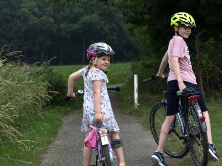 zwei Kinder sitzen auf ihren Fahrräder und blicken zurück